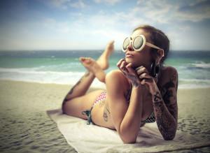 Tattooed girl sunbathing on the beach